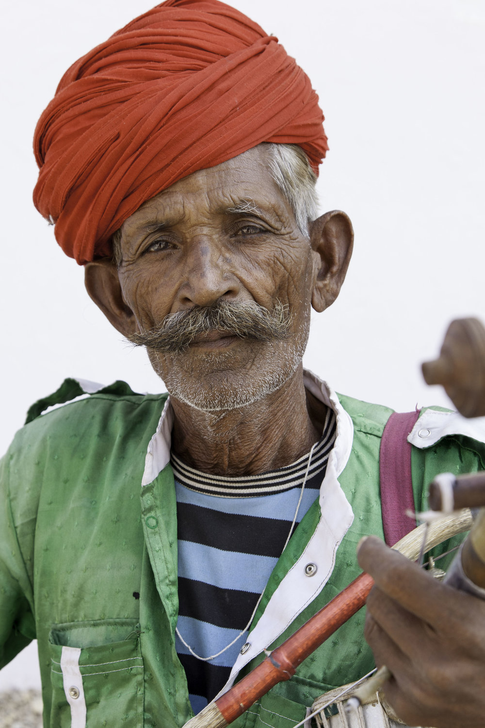 A street musician with his  Ravanahatta , a single stringed instrument with an underslung, coin purse-like bag, or bells attached to the bow. He played beautiful, wailing melodies on the string while occasionally jostling the  instrument for a bit of a chingy percussion accompaniment.