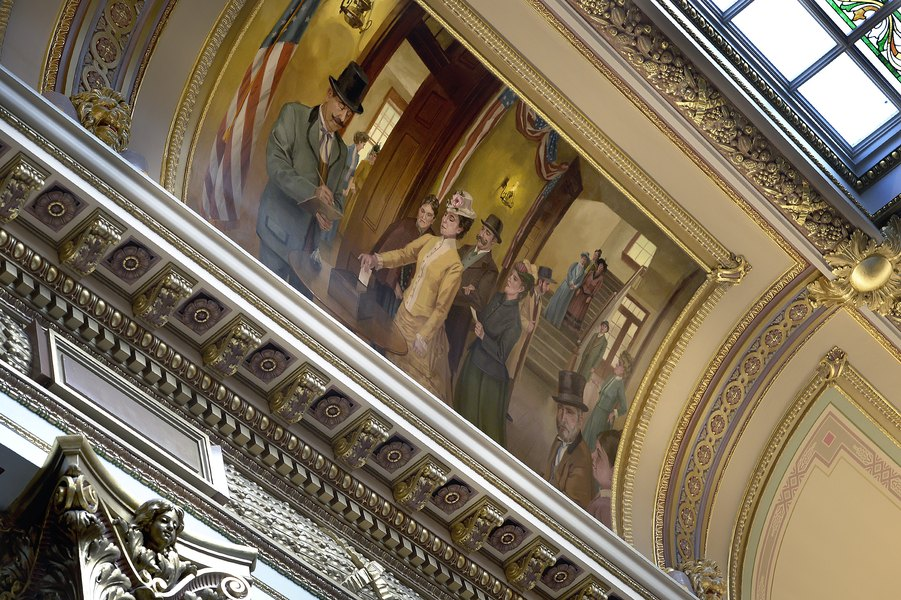 This mural by David Koch hangs in the Utah State Capitol Building and shows Seraph Young casting the first female vote.