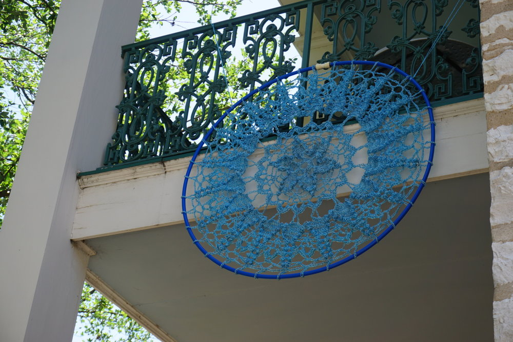 "The ""outdoor doilie"" is made from repurposed string collected from hay bales and strung across a hula hoop."