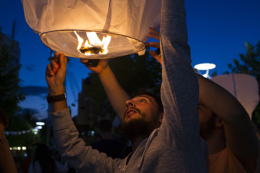 A man holds a lantern before setting it off on July 20, 2016 in Pristina, Kosovo. Lighting lanterns was part of HAPU, a festival of artwork that is displayed in public spaces.