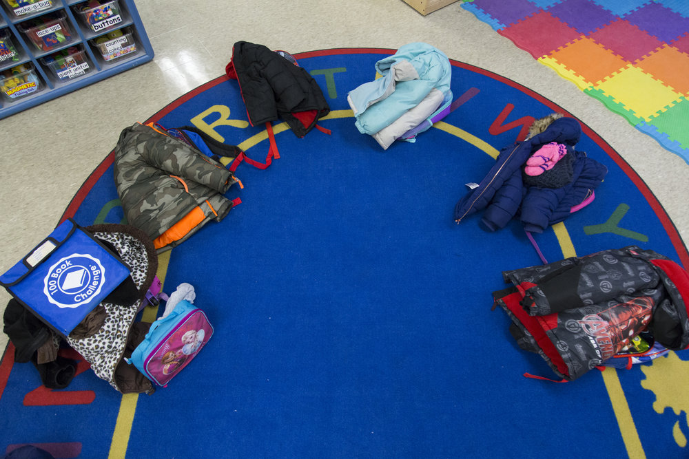 Backpacks are laid out on a rug before the parents come to pick up the children.