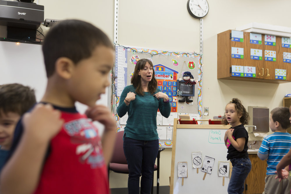 Christine Herne leads her class in a song that teaches them to say 'hello' in different languages.