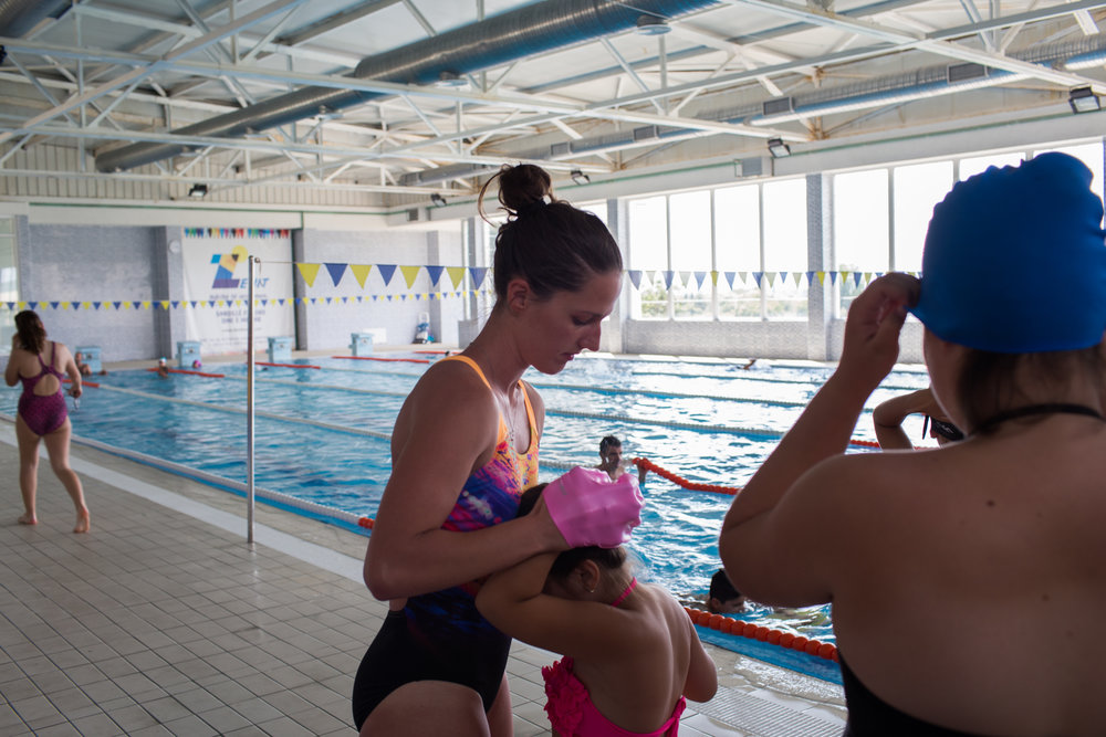 Kaltrina assists a child in putting on a swim cap before getting into the pool.