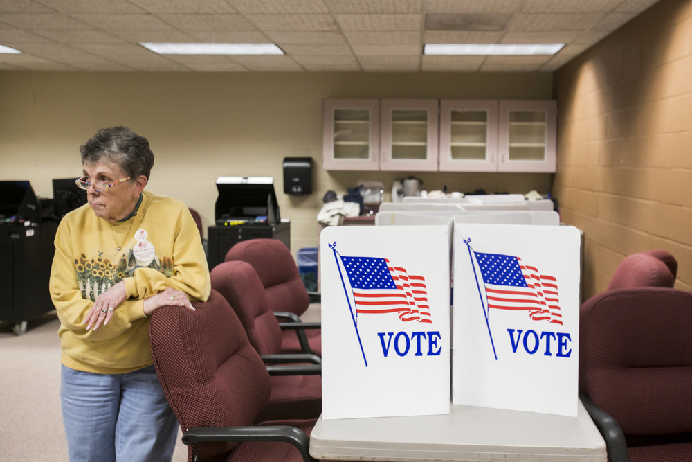 Polly Orlebeke, an election inspector, rests on a chair during a lull while waiting for people to vote at Penfield High School in Penfield, N.Y. on Nov. 8, 2016. Orlebeke arrived at the school at 5 am to set up and assist voters in casting ballots.