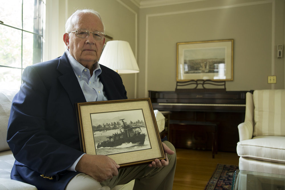 Tom Richards poses for a portrait with a photograph of swift boat, on which he served during the Vietnam War, in his home in Rochester, N.Y. (Emily Hunt/WXXI)