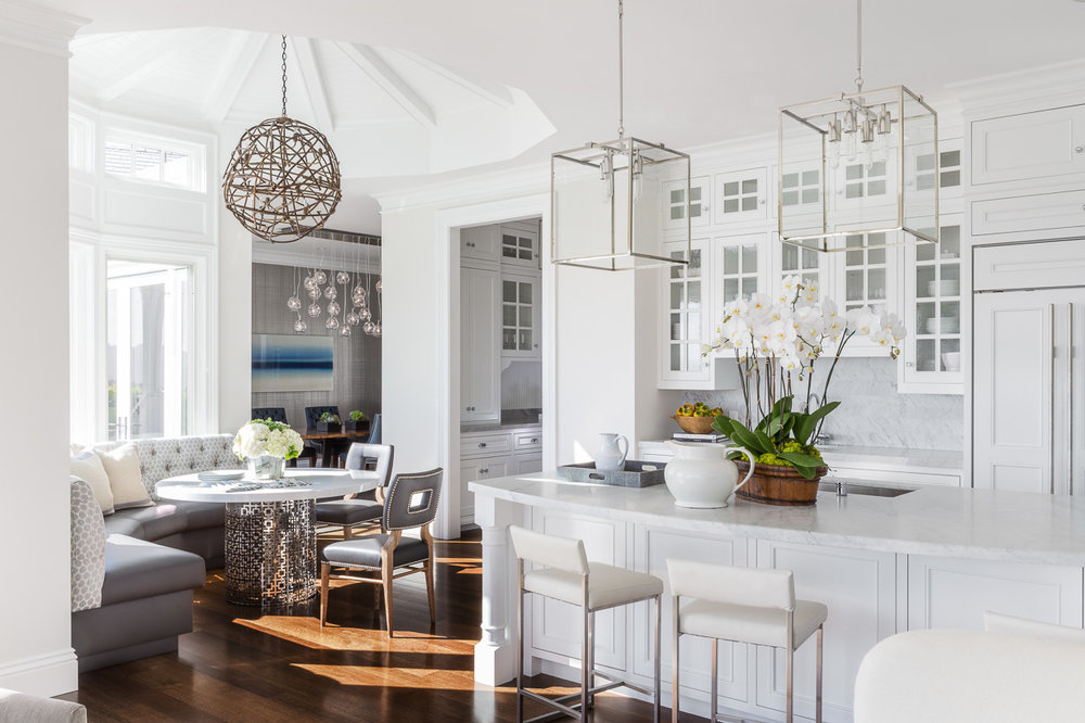 The open kitchen and vaulted breakfast nook are sheathed in a fresh white. The Jonathan Adler dining table is surrounded by Hollywood at Home chairs and a custom-made banquette, and surmounted by an organically shaped pendant light from San Francisco's Robinson Finishes & Design.