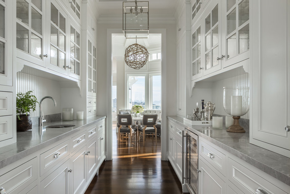 A traditional butler's pantry is tucked behind the main kitchen space. The classic cabinetry and beadboard backsplash are balanced by a minimal glass-and-chrome pendant by Dogfork.