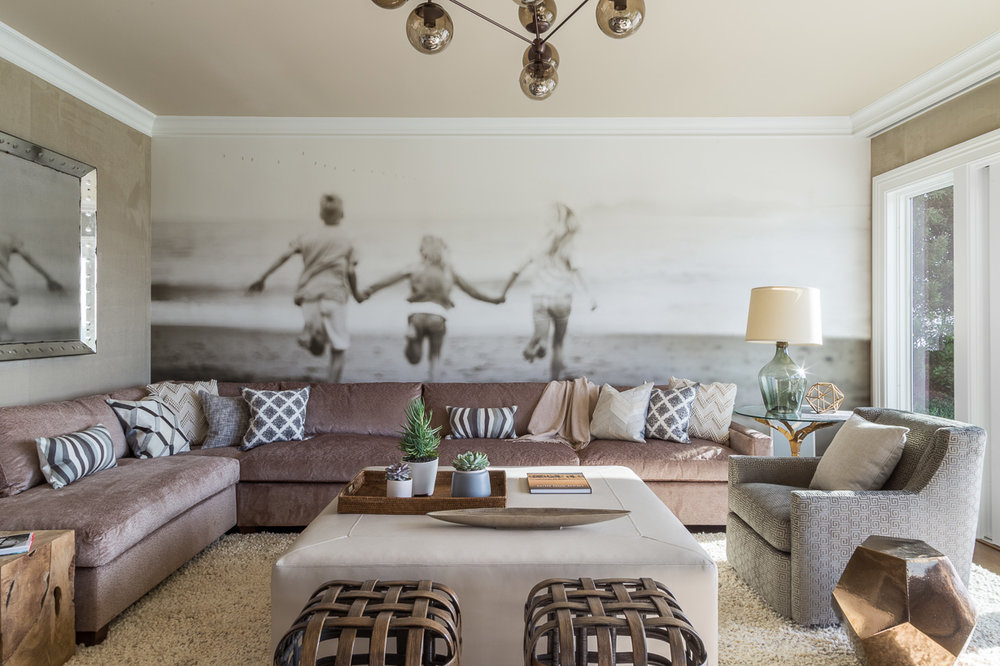 """Our media room is one of my favorites,"" says one of the homeowners. ""We had a very talented photographer take an intentionally slightly blurry photo of our children running toward the beach and blew it up to be wallpaper."" The remaining walls are covered in a Phillip Jeffries suede. The raw wood side table is by Jayson Home, and the ceiling fixture is from Design Within Reach."