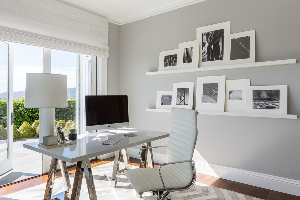 In a serene office space, a Williams-Sonoma Home desk is accompanied by an Eames-style executive chair in white leather and a chevron-pattern rug.