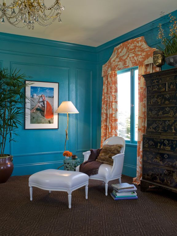 Kendall Wilkinson Design  painted these bedroom walls teal blue. Orange accents and coral toile fabric add drama.