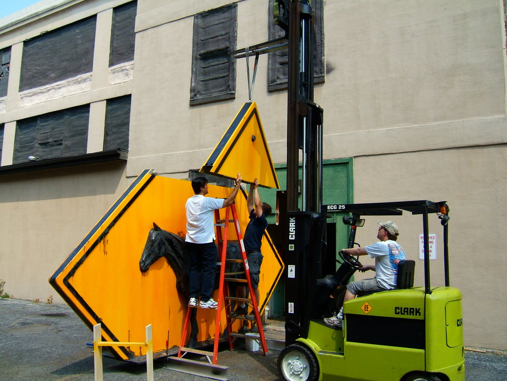 Moving the sculpture outside the shop to apply the rust actvator.  Rochester, NY 2005.