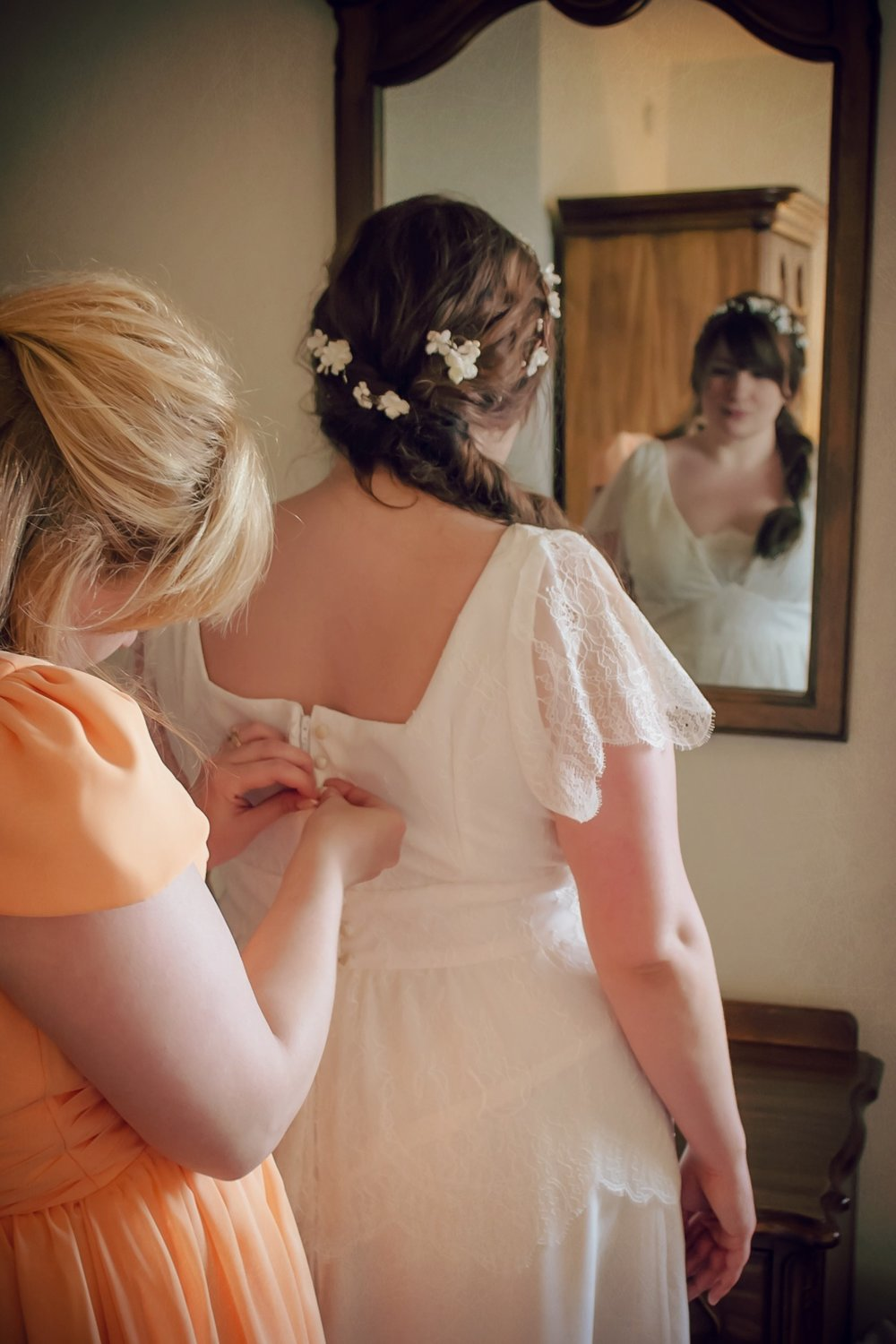 Bride in mirror, with back of dress being buttoned up. Layered lace at the hips adds interest to shape.