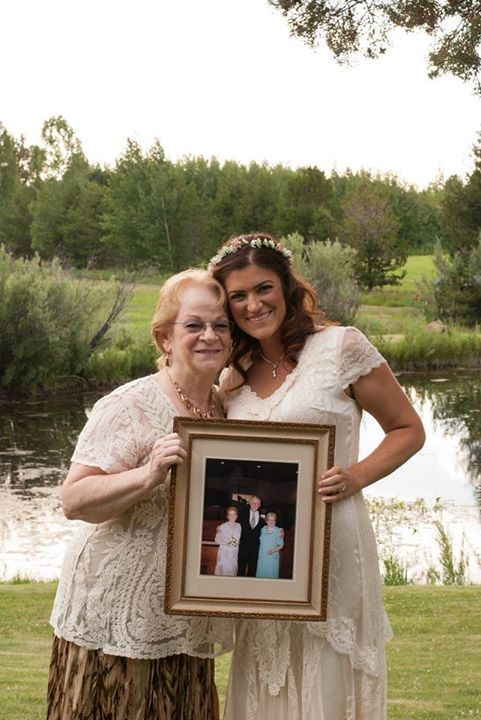 Happy bride and her grandmother pose with a photo showing the dress' original style at grandma's wedding