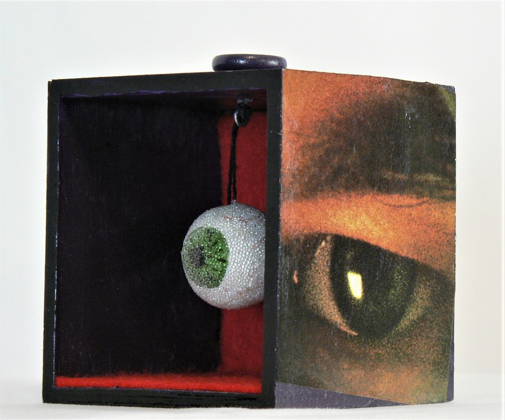 """The Eye - """"Never bend your head. Always hold it high. Look the world straight in the eye."""" -- Helen KellerMaterials: Wood box; felt; oil and acrylic paint; decorative eye; paper. Dimensions: 3""""H x 3""""W x 3""""D. Created: March 2018.Status: For Sale ($100)"""