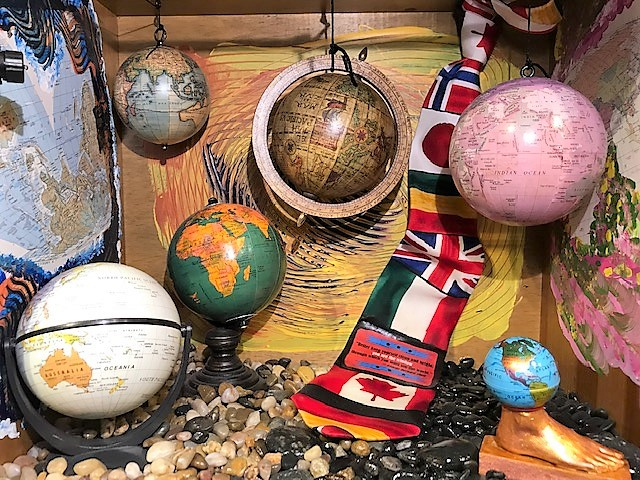 """Going Global - """"Better keep yourself clean and bright; you are the window through which you must see the world."""" -- George Bernard ShawMaterials: Wood desk drawer; globes; postage stamps; latex rubber foot; twine; light; silk tie; pebbles; acrylic paint; paper; ink. Dimensions: 15""""H x 17""""W x 11""""D. Created: June 2018.Status: For Sale ($500)"""