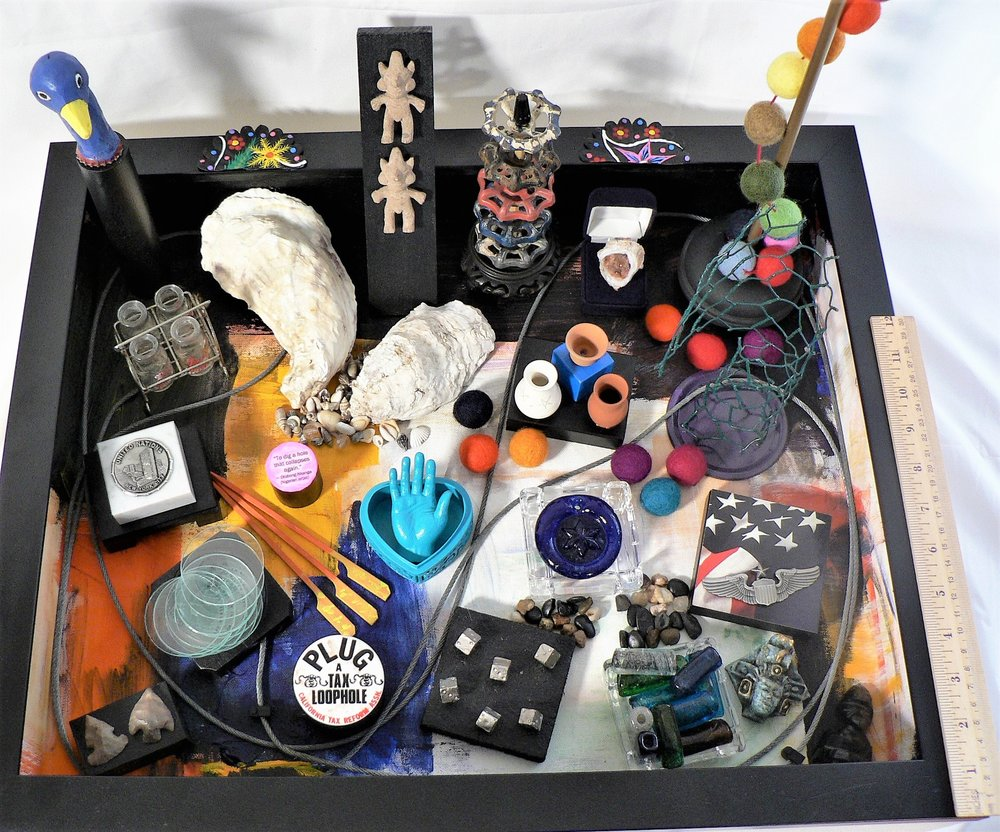 "Canvas of Curiosities - ""To Dig A Hole That Collapses Again"" -- Otobong Nkanga (Nigerian artist)Materials: Jerusalem glass beads; tax reform campaign button; glass casino ashtrays; paper; acrylic paint; crystal rock; jewelry box; wood frame; purpose-built wood box; Napalese felt garland; rubber cord caddy; practice canvas (anonymous artist); wooden Oriental vase stands; metal faucet handles; broom handle; track light glass lenses; miniature ceramic vases; rubber latex hand; toy milk bottles; Indian heart box; American Indian arrow heads; Mayan ceramic figurines; chicken wire; canning jar lid; Mexican retablo fragments; USA postcard; sea shells; metal push pins; pilot's pin, wood toy block; United Nations memento; wood folk art bird; wire metal cable; Mexico souvenirs. Dimensions: 4""H x 22""W x 22""D. Created: December 2018.Status: For Sale ($500)"