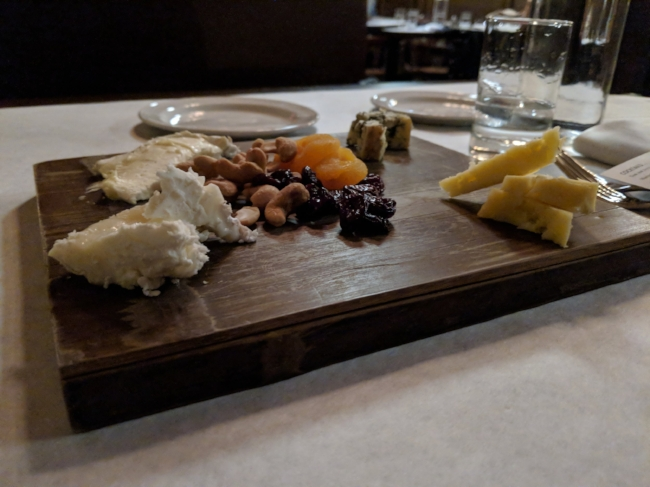 Cheese plate featuring four cheeses:  brie, gouda, blue cheese, and cheese made from cow's milk.