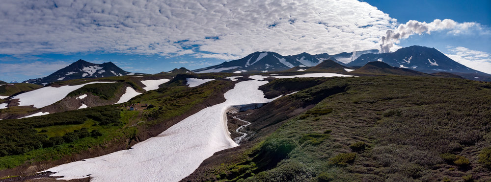 Panorama taken with my Mavic Air.  On the left you can see our final camp ground. I am standing next to a table operating the drone. In the distance, Mutnovsky puffs away. And in the foreground underneath the snow you can see two ice caves, just waiting to be explored.