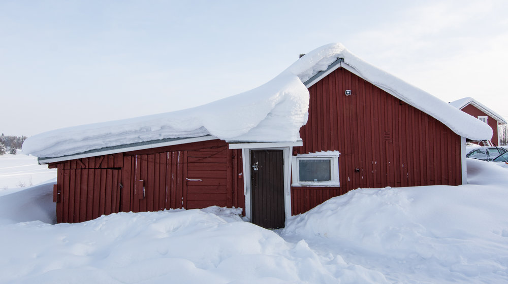 Traditional wood burning sauna in the village of Köngäs, with massive amounts of snow on its roof.