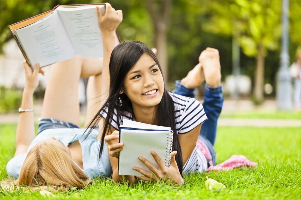 girls studying on campus lawn