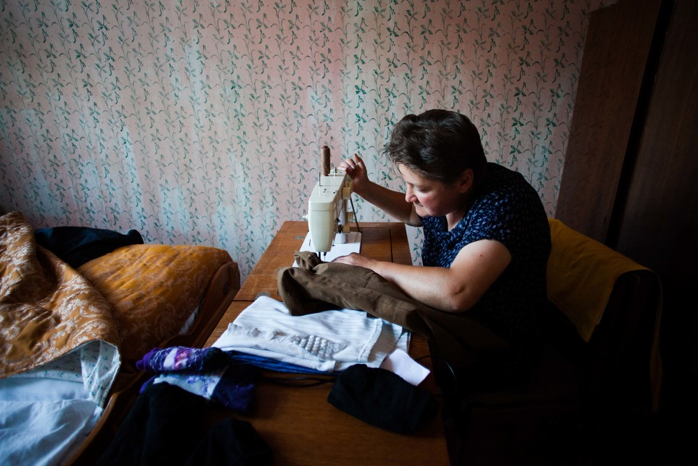Manush, a Spitak resident, spends the morning mending clothes. Her husband lives and works in Russia in order to send money back home to Armenia. This is a common situation for many families.