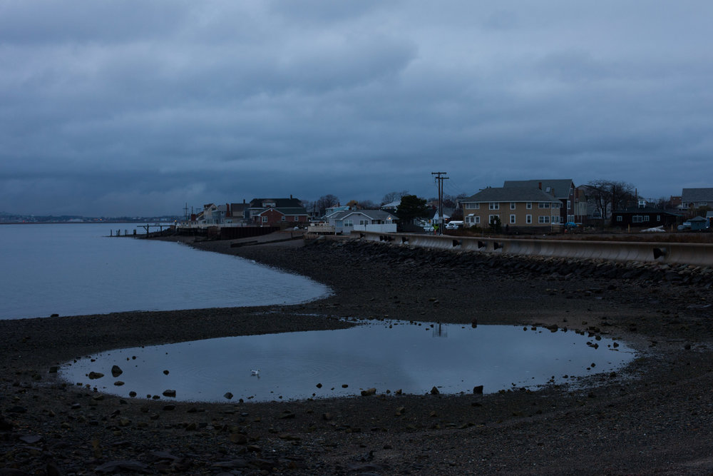 """In the winter of 1676, Christian Native Americans were moved from 'praying towns' in Massachusetts to Deer Island, just outside of Boston. The island was used as an internment camp and as many as 500 tribal members died of exposure and starvation; they were left without food or blankets.  Now, the peninsula (no longer an island), is used for a water waste treatment plant. A stone at the beginning of a walking path reads, """"The law secures to the people the right to a clean harbor."""""""
