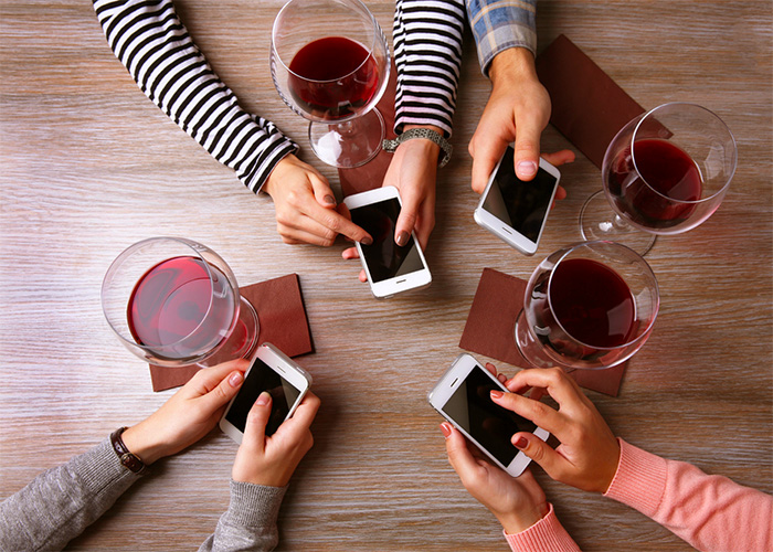 Four hands with smart phones holding glasses with red wine, on wooden table background; Shutterstock ID 360785996; PO: license(26950)