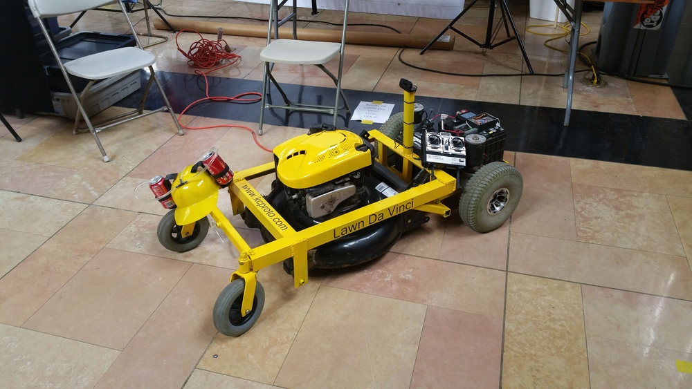 "So, you want to make your own remote controlled lawn mower like in the movie ""Honey, I shrunk the kids"" ?  You should.  This is a fun project that is very practical and makes mowing the lawn a lot more enjoyable.  You will learn a few new skills along the way that will help you be a better maker.   First, a disclaimer.  Robots are dangerous.  Lawn mowers are dangerous.  Robot lawn mowers are the danger of mowers times the danger of robots.  KC Proto is not responsible for any damage to anything living or inanimate. This project was possible because of the spirit of open source.  Pay anything you learn forward.  Suggestions on improvements are welcome.    I. Gathering materials   There are a lot of parts to this project and a few ways to customize it to suite your purposes.   These are the supplies I used and they work well.  1.  Lots of angle iron and steel-  I used 2 inch angle iron and, in retrospect, it was a little bit of an overkill.  It is strong enough for me to ride though.  2.  Mobility scooter motors- There are a lot of used motors on ebay and they are all pretty similar.  If you can get them with the tires on, it will save you a lot of time.  3. Lawn mower - Find a cheap push mower.  Any mower should work but make sure it is reliable and it starts.   4. RC remote- I used a Tower Hobbies System 3000 and it works well.  5. Other electronics- There are a few ways to do this but I used an arduino pro mini, a raspberry pi, a Sabertooth 2x25 motor controller, a relay and a webcam.  More on this later.  6. 2 Batteries- Pretty much any 12v car or marine battery should work.  2 trickle chargers fill up the batteries in between mowings.  7. Beer hat- Optional, but highly recommended."