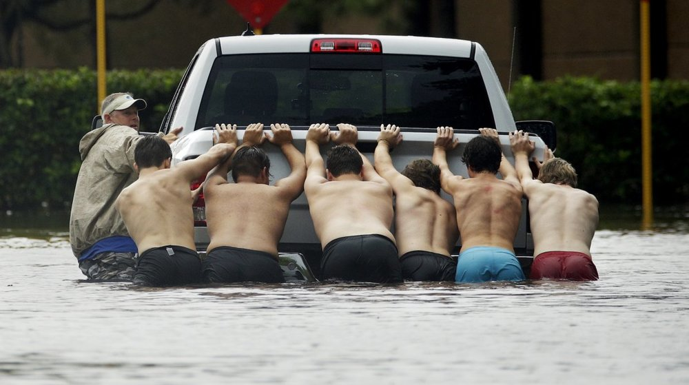 a-group-of-men-pushed-a-stalled-pickup-truck-through-a-flooded-street-in-houston-texas.jpg