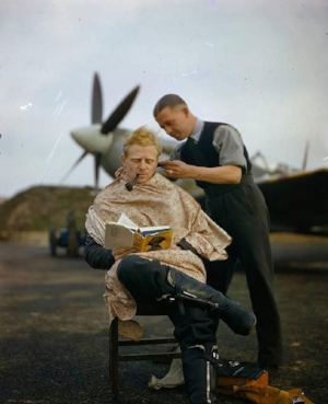 RAF pilot Francis Mellersh getting a haircut and reading Greenmantle by John Buchan. Essex, England, 1942.