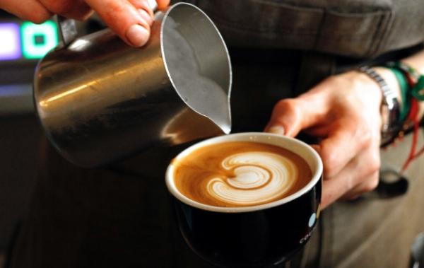 Barista versant du Latte Art à Coutume Café
