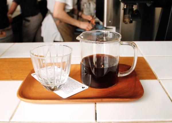 Café filtre joliment présenté malgré l'agitation derrière le bar - Coutume Café à Paris