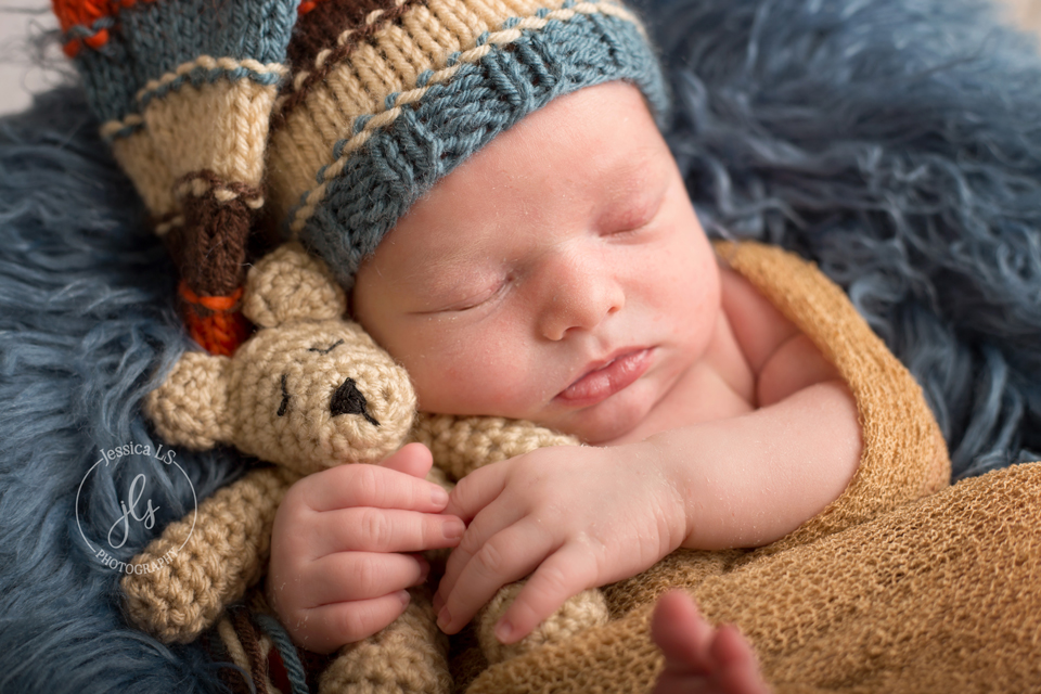 newborn baby boy snuggled with bear