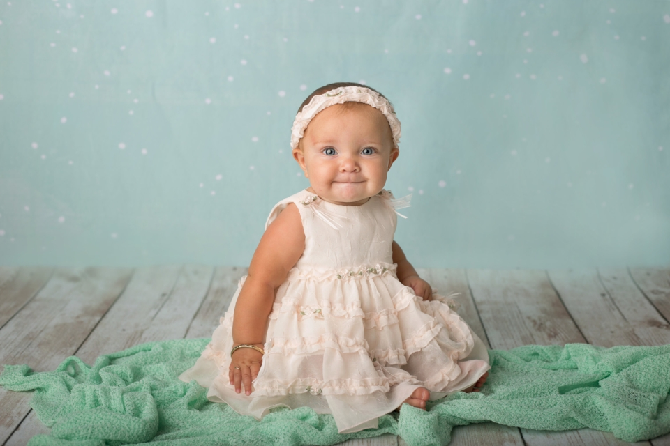 6 month baby girl in studio with mint green blanket