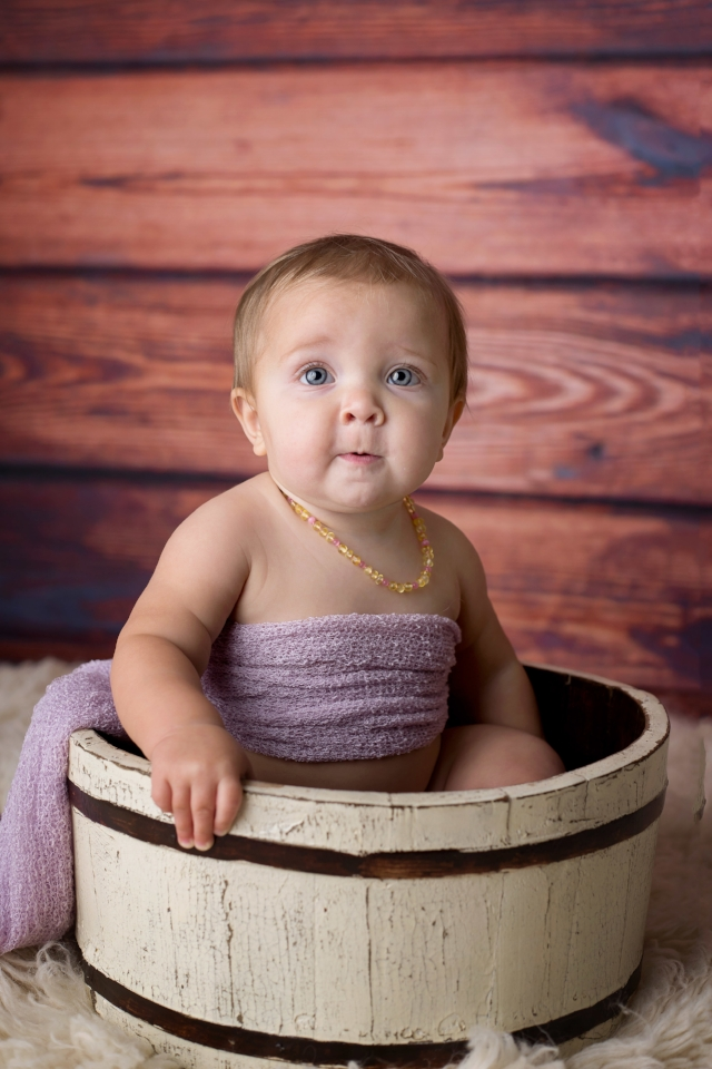 9 month baby girl in wooden bucket