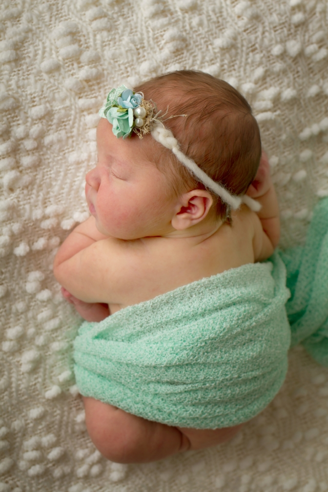 newborn baby girl wrapped in mint