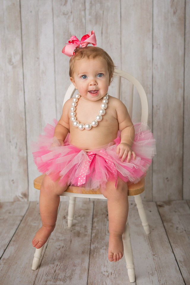 pretty little girl in pink tutu sitting in chair