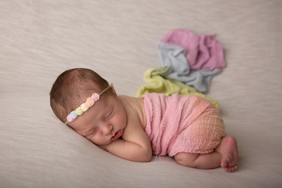 rainbow baby laying on her tummy with rainbow wrap and rainbow headband