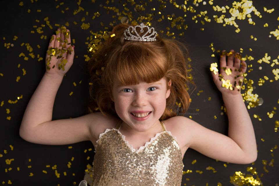 5 year old girl laying in gold glitter