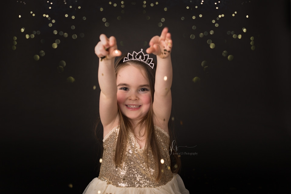 6 year old girl throwing gold glitter in the air