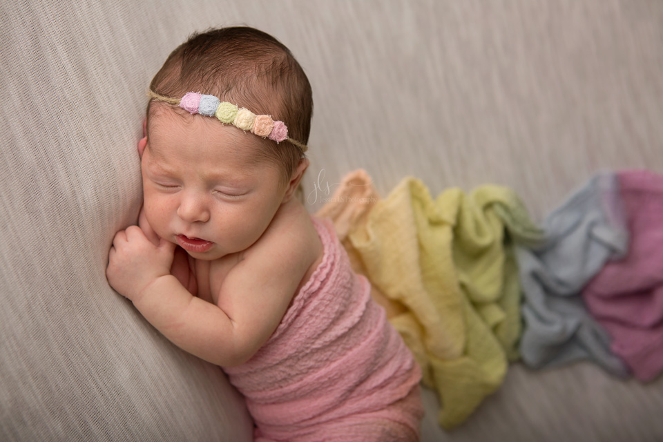 rainbow baby girl with rainbow wrap and headband in newborn studio