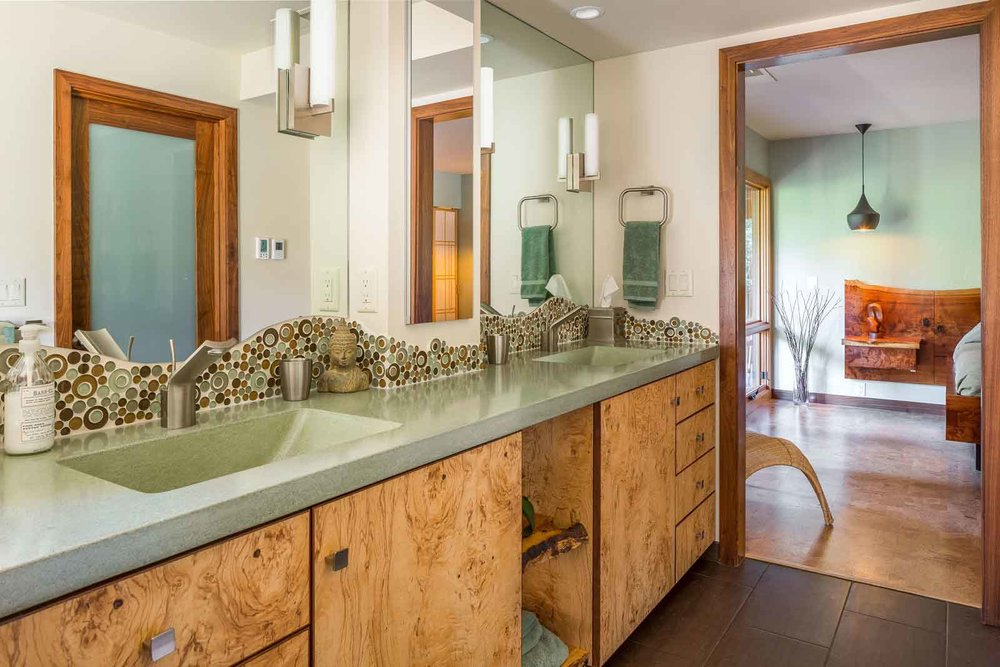 Custom olive wood vanity with cast concrete countertops with integral sinks.  Water jet tile accents in shower and vanity.