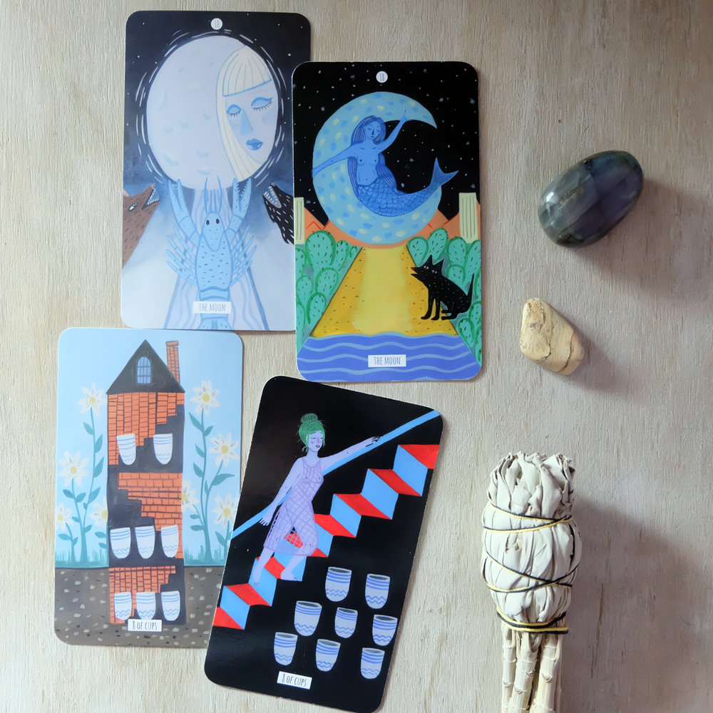 "The Moon from both decks combined, I feel, make a pretty good rendering of the Rider-Waite Smith card. I feel like the crayfish of the ""How to Deal"" card pulls the eye towards it, but the Circo Tarot's dog (wolf?) grabs my attention more. I love the mermaid figure, though!  The 8 of Cups from the ""How to Deal"" deck takes a little more time for me to figure out. From the get go, I'm thinking that farewells, though sad, do make a solid foundation for emotional growth. The Circo Tarot version just looks like a more obvious interpretation of the goodbyes the 8 of Cups is known for."