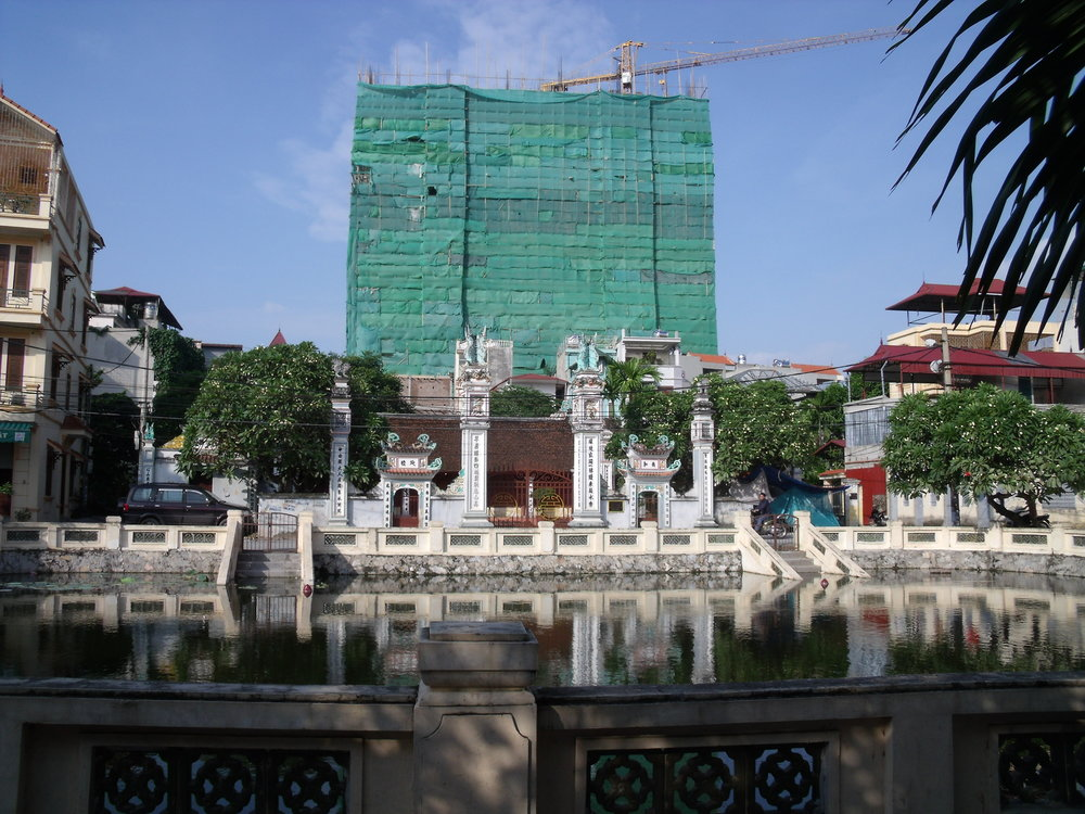 A new high-rise building overlooks a temple in one of Hanoi's many urban villages. Photo by Danielle Labbé.
