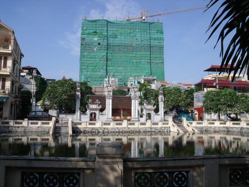 Une nouvelle tour en construction derrière la maison communale d'un des nombreux villages urbains de Hanoï. Crédit: D.Labbé