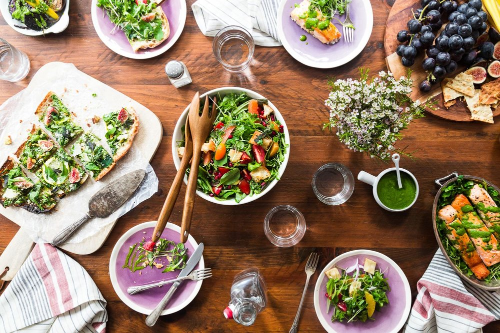 overhead of dinner table with baby greens recipes