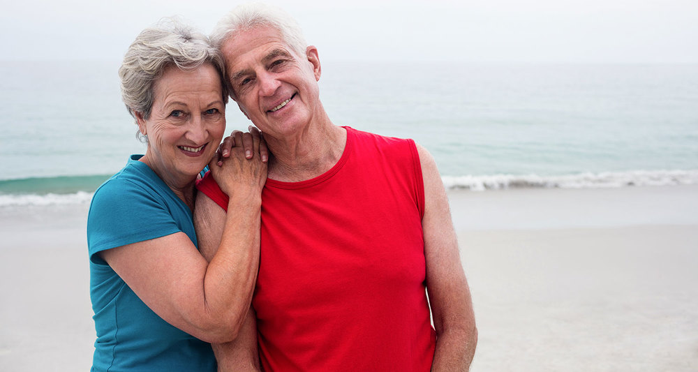 Older couple walking on beach photo
