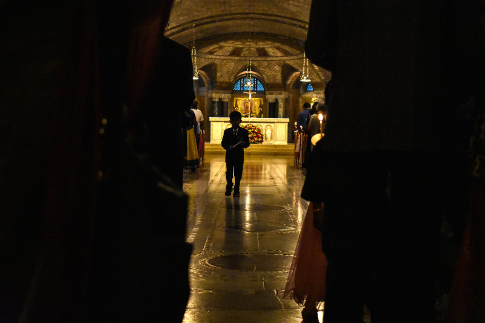 A young boy walks down the aisle of the Crypt Church at the Basilica of the National Shrine of the Immaculate Conception in Washington, Saturday, Sept. 8, 2018. Hundreds of Catholics of South Asian descent convened for the Indian American Catholic Association's 21st Annual Pilgrimage to Our Lady of Good Health, Vailankanni. The Blessing and Dedication of Children ceremony took place in the Crypt Church. (Lindsey Leake/American University)
