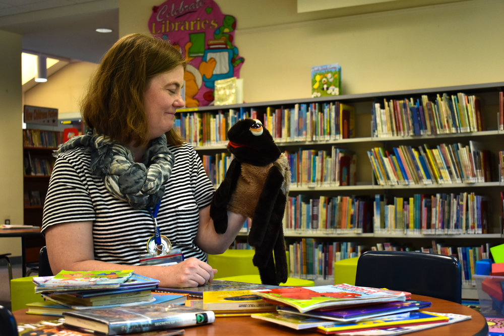 In this Saturday, Sept. 29, 2018, portrait, youth services librarian Leticia Van Campen poses with a stuffed puppet at George Mason Regional Library in Annandale, Va. (Lindsey Leake/American University)