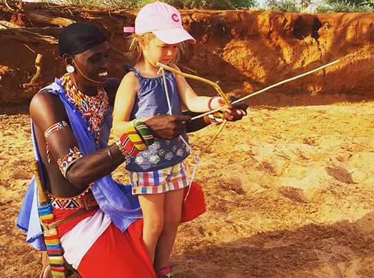 Farley's daughter learning archery from the Maasai